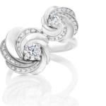 """Sertie de deux diamants en son centre, la bague Aria """"Toi et Moi"""" rend hommage à la chorégraphie de lumière à travers ses courbes délicatement pavées et entrelacées. Poids total : 0.97 carat (dont 2 diamants de taille brillant de 0.30 et 0.15 carat)."""