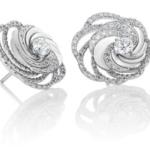 Une énergie rayonnante se dégage des deux diamants sertis au centre de ces délicates boucles d'oreilles Aria. Le contraste entre l'or blanc, le pavé et le geste Aria aérien attire la lumière et révèle l'énergie intérieure des diamants. Poids total : 1.71 carat, dont un diamant central de taille brillant de 0.30 carat.