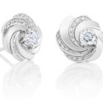 Des courbes d'or blanc et pavées s'entrelacent grâcieusement autour du diamant central de 0.15 carat de ces puces d'oreilles Aria. Les courbes pavées créent un rythme qui accentue le mouvement, tandis que la lumière s'invite dans une danse autour des diamants et rayonne d'un éclat exceptionnel. Poids total : 0.36 carat (dont deux diamants de taille brillant de 0.15 carat).